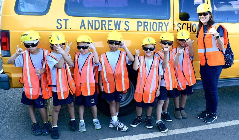 Kids from St. Andrews school holding up shakas and posing in hard hats and safety vests